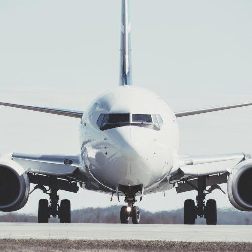 A passenger jet taxis towards an airport gate after landing.